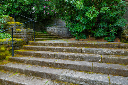 Old stone stair steps in Renaissance garden with plants and shrubs during spring season Stock Photo