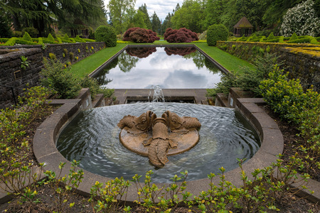 Dolphins trio water fountain and reflection pond in symmetrical Renaissance garden