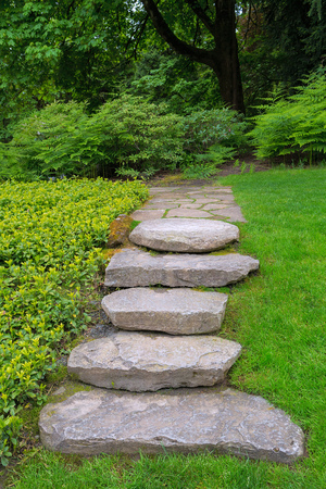 Large rocks stone steps stair and flagstone path in lush green backyard garden