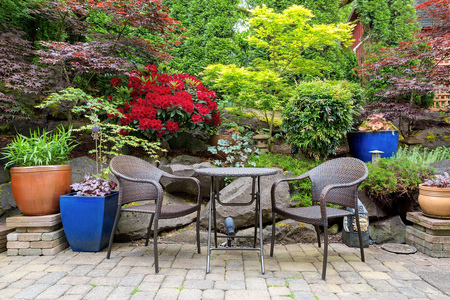 Garden backyard with lush plants landscaping and stone paver patio hardscape with wicker bistro furniture chair and table set in spring season