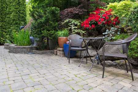 coral bark: Garden backyard with lush plants landscaping pond water fountain and stone paver patio hardscape with wicker bistro furniture chair and table set Stock Photo