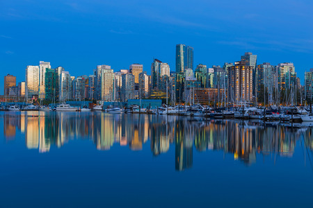Vancouver British Columbia Canada city skyline by the marina during evening blue hour with water reflection Stock Photo