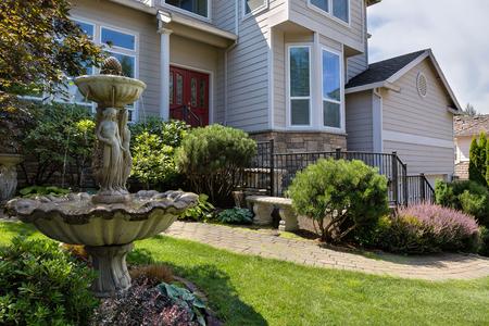 Residencial único hogar en los suburbios de América del Norte frontyard con jardín cuidado verde adoquín de ladrillo banco de la calzada y fuente de agua de piedra Foto de archivo - 86998695
