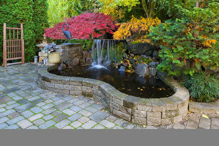Home garden waterfall pond with brick paver stone hardscape and trees in fall season colors