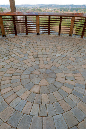 Garden Backyard circular brick stone pavers hardscape patio with wood railings stone wall view deck
