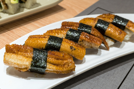 Unagi Eel Sushi wrapped over rice with seaweed on white ceramic plate closeup macro