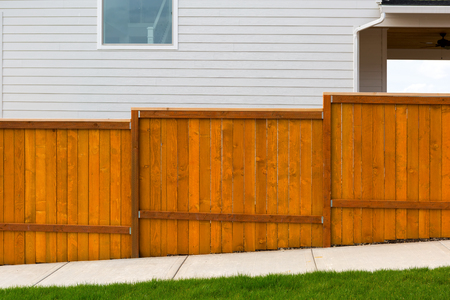 New home backyard red stained cedar wood fence construction Imagens