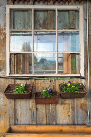 Old house window with flower planters in rural farm