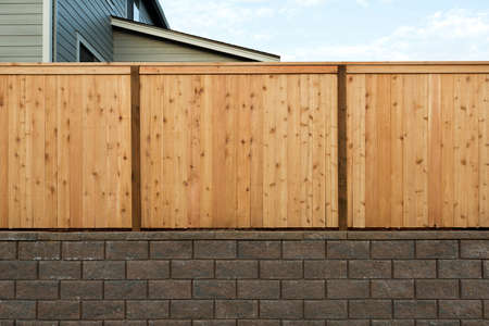 House wood fence over concrete stone retaining wall in suburban neighborhood