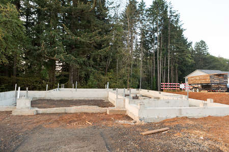 Poured concrete foundation for new house construction in suburban neighborhood Stock Photo