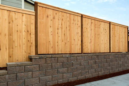 Wood Fencing on concrete stone retaining wall on sidewalk of home