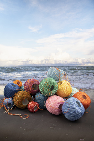 studio shot of colorful threads with seaside background