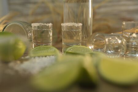 Many slices of lemon accompanied by shot's of tequila - Close-up