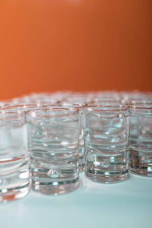 Vertical image of tasty tequila served in shots on a white table and an orange background - Close-up 스톡 콘텐츠