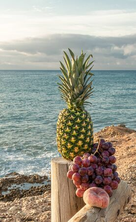 A green pineapple, a cluster of large grapes accompanied by a beautiful flat peach on a rustic wooden dock - The sea and cloudy sky in the background - Large dark red grapes - Vertical orientation