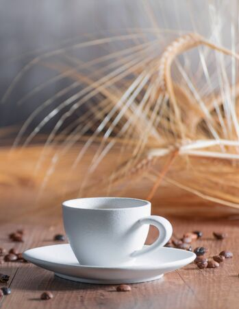 A bouquet of wheat behind a white porcelain cup with coffee beans on the wooden table. Relaxation concept and coffee aroma. Vertical image Imagens