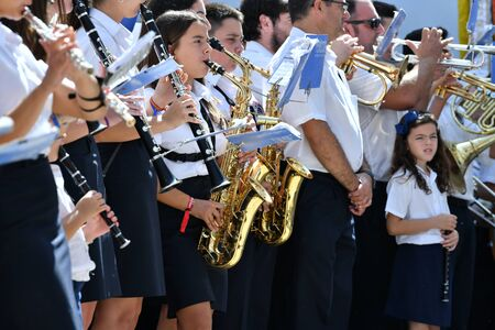 Peniscola, Castellon, Spain, September 08, 2019: Detail photo of a girl playing the saxophone surrounded by other boys who play the clarinet at the patron saint festival of Peniscola, on a sunny day. Concept of cultural celebration. Colorful photo 스톡 콘텐츠 - 133337919