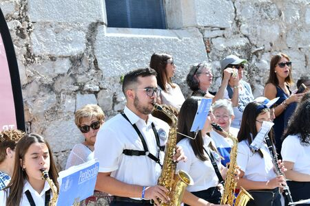 Peniscola, Castellon, Spain, September 08, 2019: Colorful photo of a boy accompanied by girls, they play saxophones in the patronal feast of Peniscola, many tourists observe, in a sunny day. Concept o 報道画像