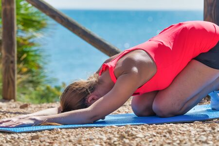 Photo detail of a beautiful girl dressed in sportswear, doing yoga on the terrace, with the sea in the background. Concept of healthy life with exercises. Colorful photo