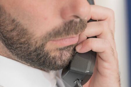 Photo detail of a man with a beard talking on the phone. Close-up Stock fotó