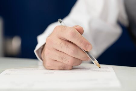 A close-up view of a man holding a pen while he writes on a sheet of paper. Фото со стока