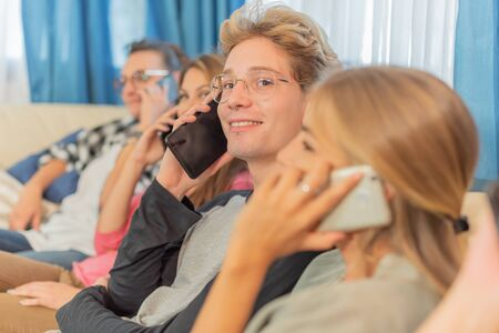 A young, smiling man watching the camera, with his friends sitting on a sofa, talking on their smart phones, in the afternoon, with a selective approach. Concept of sociable youth.