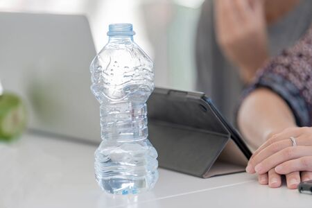 Transparent bottle of water placed on a table in which there is a black laptop with the background out of focus. Close-up.