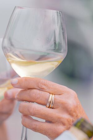 Photo detail of two hands together holding two glasses of white wine. Concept of celebration. Close-up Stok Fotoğraf