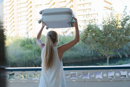 Rear view of a blonde woman lifting a gray suitcase over her head on a hotel terrace. Vacation concept, colorful photo