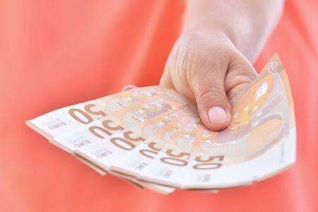 Close-up of female hand presenting banknote of 50 euro. business concept. Stock Photo