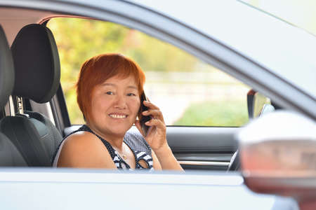 Smiling Asian woman looks at the camera and speaks on the mobile phone while driving a gray car. travel concept.