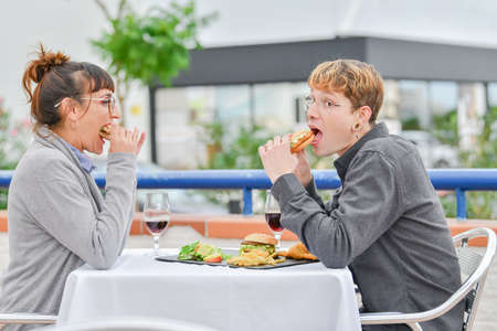 Friends or couple eating fast food with burger and fries in American fast food diner. Lifestyle concept.