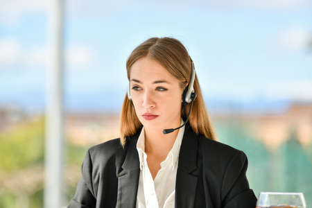 Secretary working with headset and looking to laptop. Secretary concept. 免版税图像