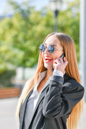 Businesswoman walking to work on morning. Happy woman talking on phone. Woman boss concept.