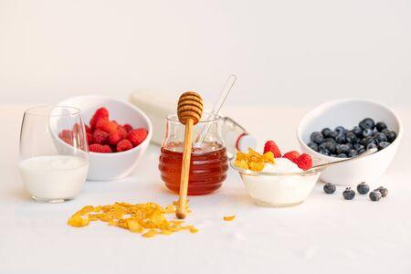 Tarro de cristal de miel con cucharón, rodeado de leche, cereales y bayas variadas. Concepto de estilo de vida saludable. Foto de archivo