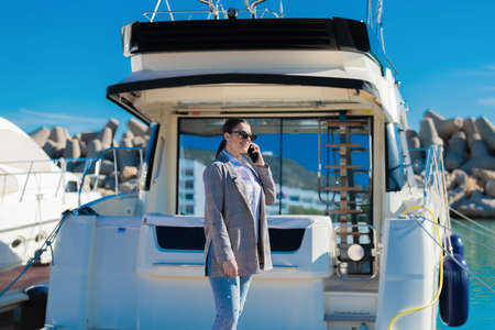 Smiling woman talks on her phone while standing on a docked boat in a sunny day. Leisure concept. Imagens