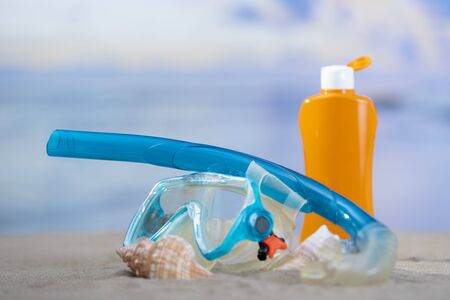 Close-up of a pair of diving goggles surrounded by seashells with an opened orange sunscreen bottle behind on an out of focus background. Summer vacation concept.
