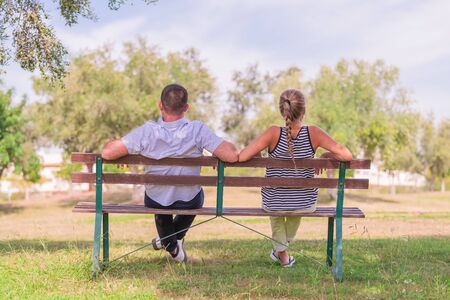 Couple sitting in a bench at a public park