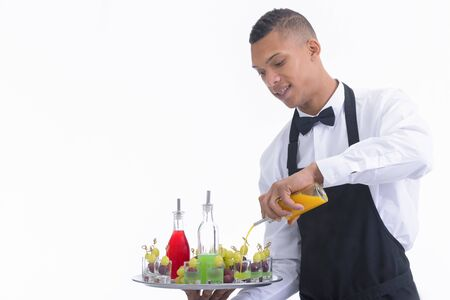 Waiter mixing liquor in glass shots with grapes