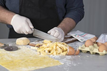 Close-up of a male chef cutting a roll of homemade pasta into noddles on a cutting board with eggs and eggshells on an out of focus Imagens