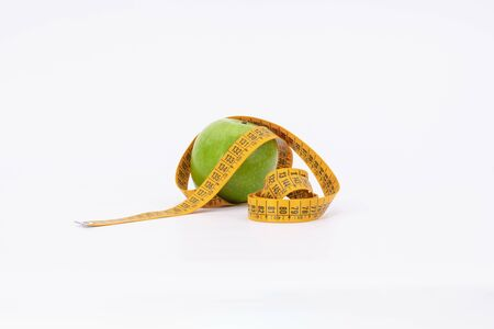 delicious green apple with measure tape as symbol for diet and weight control Archivio Fotografico