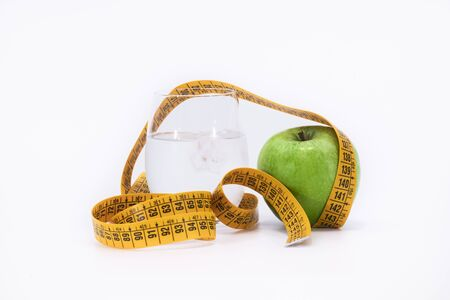 yellow tape measure and a green apple