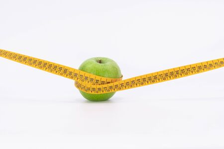Green Apple with measuring tape for diet and weight control on a white background