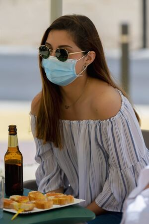 Young woman wearing sunglasses and a surgical mask enjoying a snack and a beer sitting at an outdoor bar terrace. New lifestyle concept.