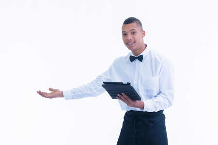 Young waiter doing a welcoming gesture while holding a tablet on a light background. Work and service concept.