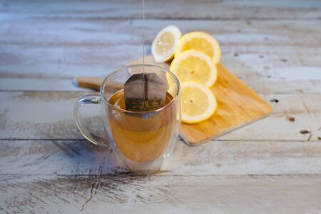 Close up of a cup of tea with a dipping tea bag and an out of focus cutting board with a sliced lemon at the back on a wooden table. Relaxation and lifestyle concept.