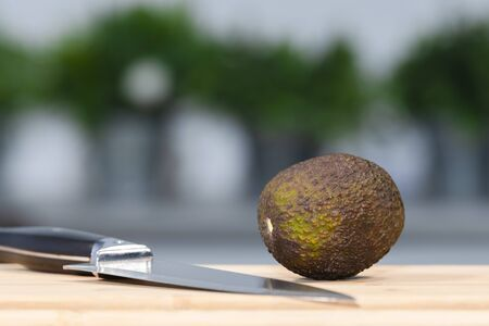 Close up of a whole avocado next to a kitchen knife on a wooden board on an out of focus background. Healthy food concept.