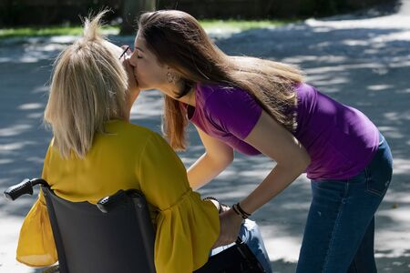 Woman lovingly kissing her wheelchair user mother on the cheek Stockfoto