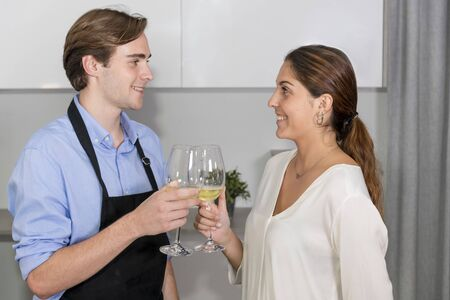 Young couple smiling at each other and toasting with two glasses of white wine at the kitchen on an out of focus background. Cooking at home and fun concept.
