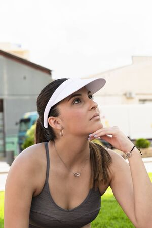 Close up of a young beautiful woman with sport visor and sport bra with her hand under her chin on an out of focus background. Healthy lifestyle and sport concept.